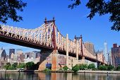 Queensborough Bridge in Midtown Manhattan with New York City skyline over East River as the famous landmarks viewed from Brooklyn. poster