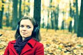 Girl in a red coat in the autumn park listening music (crossprocess)