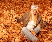 Photo of cute blonde girl throw up dry autumnal leaves