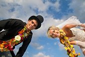 Groom with bride wearing lei looking in camera against blue sky
