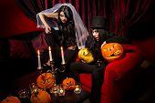 Halloween concept: sexy ladies vampire with halloween pumpkins over red background