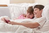 Children In Bed Playing Game Console. Close-up.