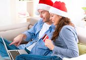 Christmas Shopping On-line . Happy Smiling Couple Using Credit Card to Internet Shop. Young couple w