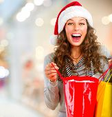 Christmas Shopping. Happy Woman with Shopping Bags in Shopping Mall.Sales. Christmas Gifts.Shopping