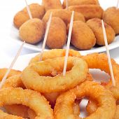 some plates with spanish calamares a la romana, squid rings breaded and fried, and croquettes served