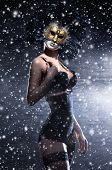 Young attractive woman in mask over winter background