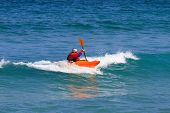 Man in a white water single kayak wearing a dry top and helmet as he rides the wave in open sea usin