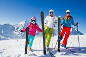 Skiing, winter fun - happy skiers on ski holiday