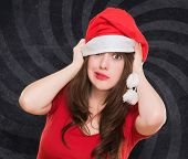 worried woman wearing a christmas hat against a vintage background