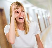 Happy Woman Looking Through Finger in a passageway