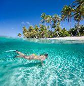 Mujer nadando en las aguas tropicales claro frente a isla exótica