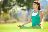 stock photo of mantra  - Pretty woman doing yoga exercises in the park - JPG