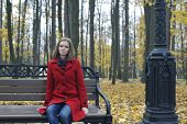 Portrait of cute girl in a red coat and jeans in the autumn park