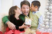 Постер, плакат: Отец существо учитывая Рождественский подарок его дочь и сын