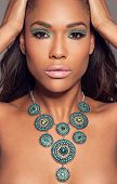 Close up head portrait of a beautiful African fashion model wearing a striking ethncs necklace posin