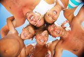 Happy Laughing Big Family Having Fun at the Beach. Enjoying Sun and Summer Holidays. Smiling People standing together in a circle against blue sky