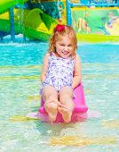 Smiling cheerful baby girl enjoying water attractions, warm sunny day, swimming in poolside, carefre