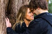 stock photo of flirt  - Close up portrait of a romantic young couple standing next to a tree - JPG