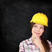 Woman architect, engineer, surveyor or construction worker wearing protection hardhat thinking looki