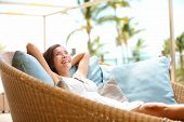 Sofa Woman relaxing enjoying luxury lifestyle outdoor day dreaming and thinking looking happy up smiling cheerful. Beautiful young multicultural Asian Caucasian female model in her 20s.