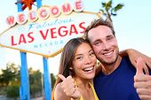 Las vegas couple happy and excited at welcome to fabulous Las Vegas sign billboard at the strip. Young multiracial people, Asian woman and Caucasian man having fun on travel in Las Vegas, Nevada, USA.