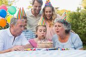Happy extended family watching girl blowing out birthday candles at picnic table outside