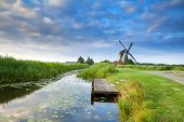 Dutch Windmill By River With Reflected Blue Sky