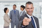 Cheerful businessman in bright office pointing at camera with colleagues on background