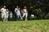 Cheerful multi generation family playing football in the park