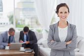 Cheerful businesswoman posing while her colleagues are working in bright office