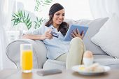 Cheerful brunette buying online while having breakfast in her living room