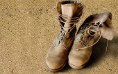 stock photo of camo  - US Army uniform boots on sandy background  - JPG