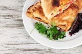 Pizza calzones on plate on wooden table