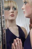 Постер, плакат: Красивая девочка подросток накрашена глядя в зеркало