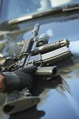 Closeup of policeman's hand picking up gun from car hood