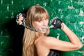 pic of sado-masochism  - beautiful woman with a steel chain in his mouth against the wall - JPG