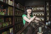 Portrait of confident female tea shop owner leaning on display cabinet
