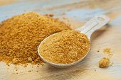 unrefinend coconut palm sugar - measuring tablespoon and pile on wood surface