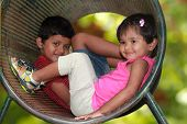 Cute Young Children(boy & Girl) Playing In Tunnel On Playground