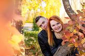 Young Couple Peeking From Behind Tree