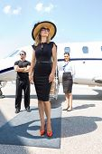 Beautiful woman in elegant dress with bodyguard and airhostess standing against private jet