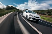 picture of speeding car  - White car cornering in mountain road with speed blur - JPG