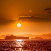 Alcatraz island penitentiary at sunset and merchant ship in san Francisco California USA