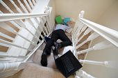 Business man falling down the stairs in the office concept for accident and insurance injury claim at work