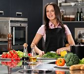 Cheerful young woman in apron on modern kitchen cutting vegetables