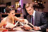Happy couple sitting with menu card in restaurant