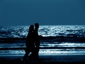 picture of moonlit  - A silhouette of a couple walking on a moonlit beach at night - JPG