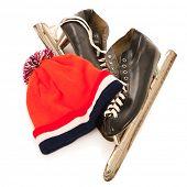 Used male ice skates and orange dutch hat isolated over white background