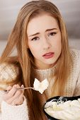 Sad, worried beautiful woman eating ice cream. Indoor background.