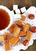 Many toffee and cup of tea on napkin on wooden table